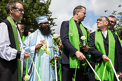 London, UK. 14th June, 2018. Faith leaders hold flowers outside St Helen's Church to mark the first anniversary of the Grenfell Tower Fire.