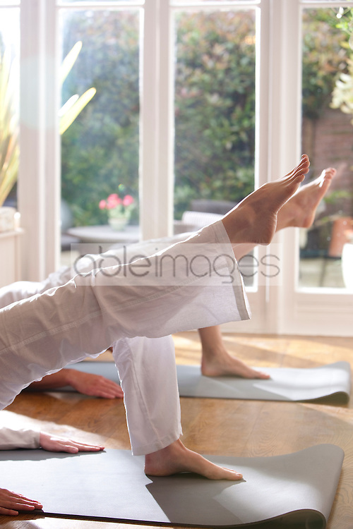 Two people during a yoga practice - headless close up