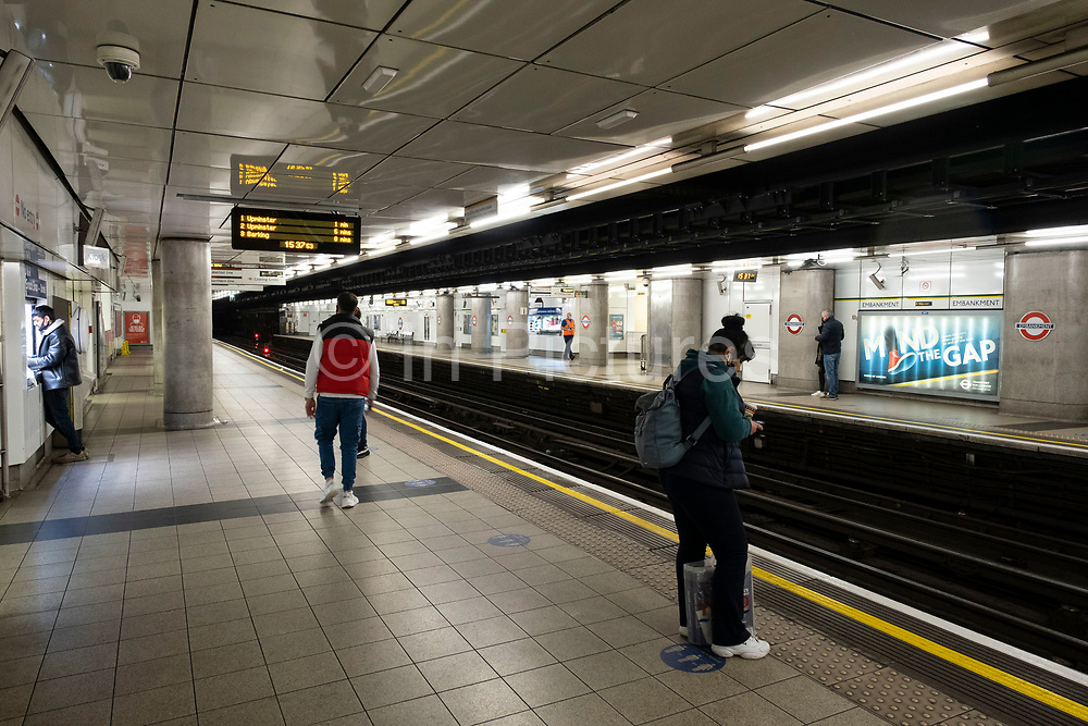 Very few people travelling on the underground as the Prime Minister announces a new tighter fourth tier of local coronavirus restrictions for London and the South East, and that the planned Christmas relaxation of the rules was to be scrapped on 19th December 2020 in London, United Kingdom. These shoppers, mostly wearing face masks were unaware, as were shop owners that the new rules were about to be announced, and this would mean that all non-essential shops will have to close from midnight.