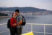 Honeymoon couple on ferry boat kiss, with town of Korcula in background. Island of Korcula, Croatia