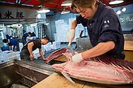 Masakazu Sato are cutting a tuna at the wholesaler Maguro Naito at the Tsukiji Market, Tokyo, Japan.