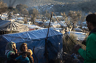 Woman talking across a net for to olives harvest used by inhabitats as a fence.  About 20000 are living in a makeshift camp nearby the city of Moria on the island of Lesbos in miserable conditions, most of the without water, electricity nor sanitary facilities.  Federico Scoppa