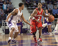 Nebraska guard Charles Richardson Jr. (R) brings the ball up court against pressure from Kansas State guard Mario Taybron (L) in the first half.  The Huskers defeated K-State 57-42 at Bramlage Coliseum in Manhattan, Kansas, January 11, 2006.