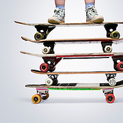 The feet of a young boy balancing precariously on a stack of skateboards ready to perform his latest stunt trick.