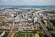 Nederland, Amsterdam, Amsterdam-West, 25-05-2010. Sloterdijk en omgeving, Teleport. Kantoorlokatie en openbaar vervoerknooppunt.  Links de spoorlijn van en naar Schiphol, Zaandam, Station Sloterdijk, kantoren van onder andere KPN en de Belastingdienst. Rechts de A10-West, richting Coentunnel, Westpoort met havens aan de horizon..Sloterdijk area, Teleport. Office Location and public transport hub. The railway links Amsterdam with Schiphol, Zaandam. Ringroad A10 West (r), towards Coentunnel, Westport with pors on the horizon..luchtfoto (toeslag), aerial photo (additional fee required).foto/photo Siebe Swart