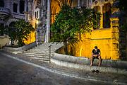 Soller, Mallorca, At Plaza de la Constituciónn, a man is listening to his phone at the Església de Sant Bartomeu. 02-08-2018