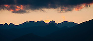 Post-sunset alpenglow lights clouds above silhouetted mountains in the NE region of the Olympic Mountains of western Washington state, USA. Boulder Mountain, Iron Mountain, the Jupiter Hills panorama