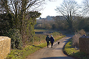 Couple walk their dog on a country lane in Asthall Leigh, Oxfordshire, United Kingdom