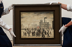 "© Licensed to London News Pictures. 30/04/2021. LONDON, UK.  Technicians present ""Going to the Match"", 1928, by L.S. Lowry at Sotheby's New Bond Street.  The painting is among the earliest of Lowry's depictions of spectators attending a sporting event. The artwork will make its auction debut at Sotheby's this summer with an estimate of £2-3m.  Photo credit: Stephen Chung/LNP"