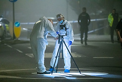© Licensed to London News Pictures. 11/11/2020. Slough, UK. Forensic investigators set up photographic equipment on a roundabout at the corner of Stoke Poges Lane and Bradley Road  A person was reportedly stabbed in Slough on Tuesday 10/11/2020. A large cordon was put in place by Thames Valley Police centred around shops on Stoke Poges Lane and included a large section of Bradley Road. Photo credit: Peter Manning/LNP