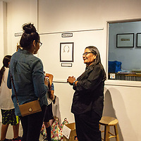 Artist Betty Holyan talks about her art project on women of the streets of Gallup Saturday night at ART123 Gallery.