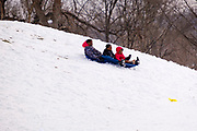 02 JANUARY 2021 - DES MOINES, IOWA: A family rides a plastic toboggan down the hill below the Iowa Supreme Court. The hill is one of the most popular spots in Des Moines for sledding and winter play. Hundreds of people took advantage the warmer weather and the week's record snow to spend time on the slopes around the Supreme Court and neighboring capitol. The high temperature Saturday was about 25F (-4C).      PHOTO BY JACK KURTZ