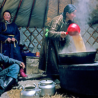MONGOLIA, Horidol Saridag Mts. Nomadic family waits for salty tea after unloading animals and pitching ger (yurt) during frigid fall migration.