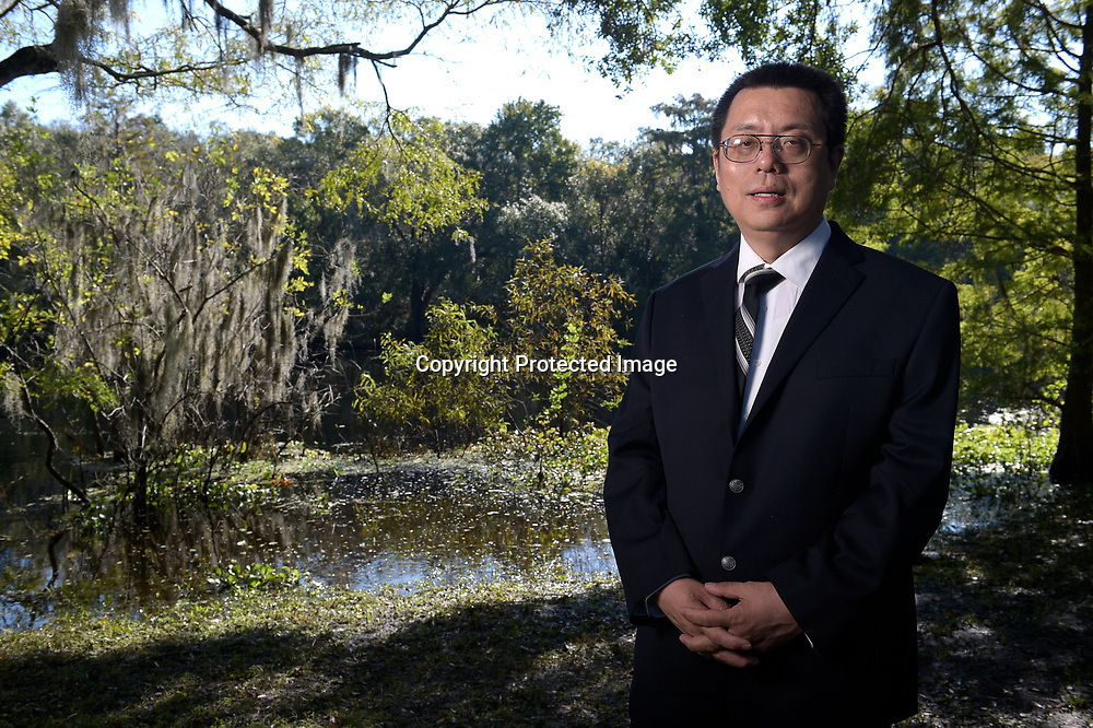 Former University of South Florida professor Dajin Peng stands for a photo at a park near the campus in Tampa, Fla., Friday, Oct. 10, 2014. Peng is on suspension from the university, where he taught international business and directed the Confucius Institute, a cultural program funded by the Chinese government. Peng claims the Federal Bureau of Investigation recruited him to be a spy. (Photo by Phelan M. Ebenhack)