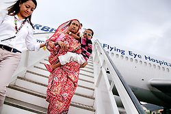 Staff Ophthalmologist Joanne Barleta escorts Awjala Devi carries her grandson, Akisul Surushe, 5, down the stairs of the Flying Eye Hospital after doctors checked on how his right eye was healing. He was one of five children who visited the plane for checkups the day after their surgeries.