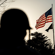 One of the statues of soldiers at the Korean War Veterans Memorial on the National Mall is Washington DC is silhouetted against the sun, with an American flag flying in the breeze in focus behind it.