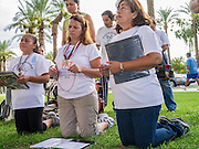 """19 JULY 2012 - PHOENIX, AZ:  People pray for justice during a vigil at the Arizona State Capitol on the first day of a class action lawsuit, Melendres v. Arpaio in Phoenix Thursday. The suit, brought by the ACLU and MALDEF in federal court against Maricopa County Sheriff Joe Arpaio, alleges a wide spread pattern of racial profiling during Arpaio's """"crime suppression sweeps"""" that targeted undocumented immigrants. U.S. District Judge Murray Snow granted the case class action status opening it up to all Latinos stopped by Maricopa County Sheriff's Office deputies during the crime sweeps. The case is being heard in Judge Snow's court.  PHOTO BY JACK KURTZ"""