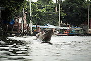 """17 NOVEMBER 2012 - BANGKOK, THAILAND:  A man runs his """"long tailed"""" boat up a canal in Bangkok. Long tailed boats use big V8 car engines and have 30-40 foot long propeller shafts that extend past the back of the boat. Bangkok used to be known as the """"Venice of the East"""" because of the number of waterways the criss crossed the city. Now most of the waterways have been filled in but boats and ships still play an important role in daily life in Bangkok. Thousands of people commute to work daily on the Chao Phraya Express Boats and fast boats that ply Khlong Saen Saeb or use boats to get around on the canals on the Thonburi side of the river. Boats are used to haul commodities through the city to deep water ports for export.    PHOTO BY JACK KURTZ"""