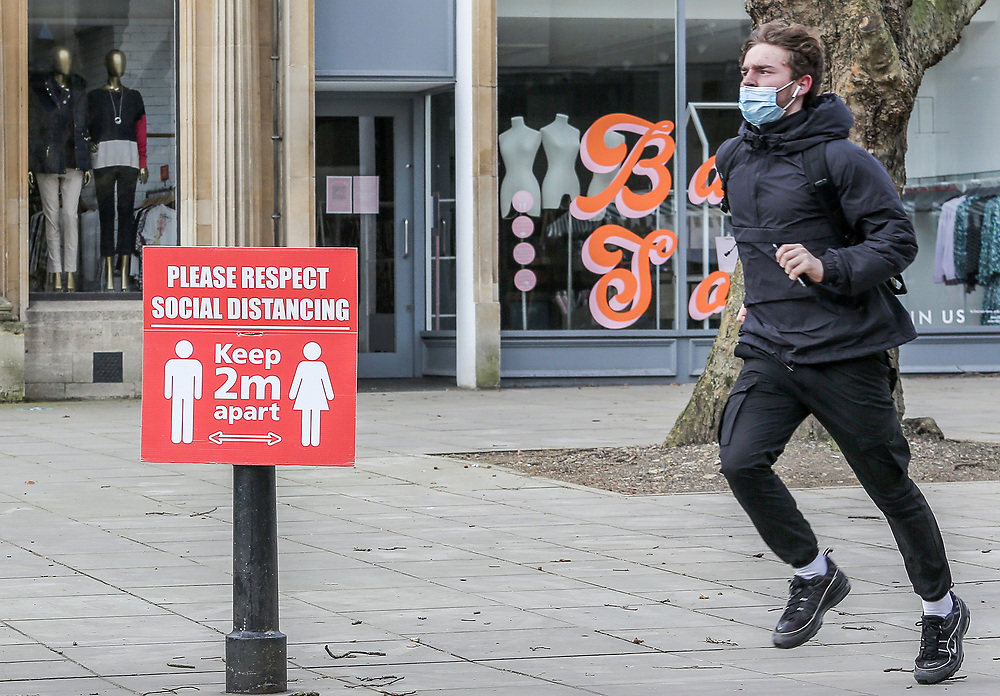 12th, March, 2021. Cheltenham, England. A member of the public runs through the town centre wearing a mask.