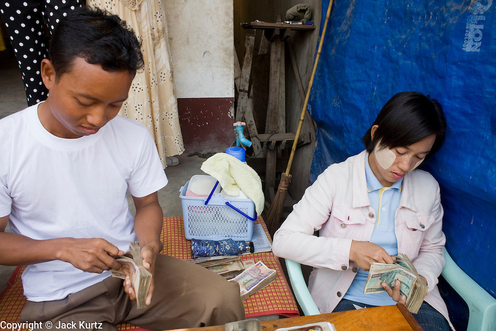 26 FEBRUARY 2008 -- MYAWADDY, MYANMAR: Black market currency traders count their Kyat (Burmese currency) in Myawaddy, Myanmar (Burma). Myawaddy is just across the Moei River from Mae Sot, Thailand and is one of Myanmar's leading land ports for goods going to and coming from Thailand. Most of the businesses in the town are geared towards trade, both legal and illegal, with Thailand. Human rights activists from Myanmar maintain that the Burmese government controls the drug smuggling trade between the two countries and that most illegal drugs made in Myanmar are shipped into Thailand from Myawaddy.   Photo by Jack Kurtz