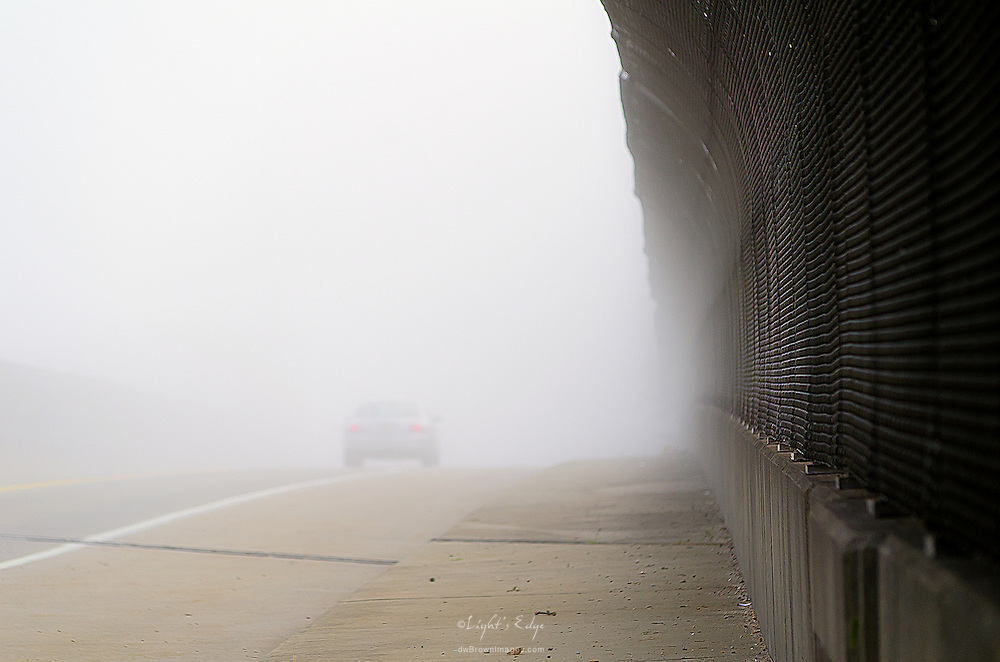 A car passes by on a fog covered overpass early on a late summer's morning.