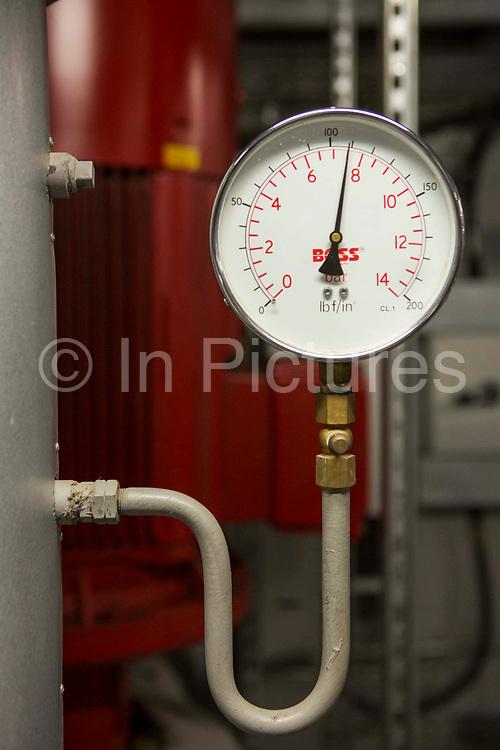 A pressure gauge inside the boiler room of a modern office building in central London UK.