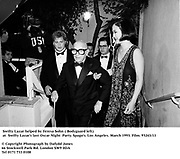 Bodyguard, Swifty Lazar helped by Teresa Sohn at  Swifty Lazar's last Oscar Night  Party. Spago's. Los Angeles. March 1993. Film. 93243/11<br /><br />© Copyright Photograph by Dafydd Jones<br />66 Stockwell Park Rd. London SW9 0DA<br />Tel 0171 733 0108