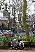 A man sitting in Pond Square, Highgate Village next to a pushchair using an Apple  computer, 25th March 2007, Highgate, London, United Kingdom. The village is at the top of North Hill which provides views across London. Until late Victorian times it was a distinct village outside London, sitting astride the main road to the north. Highgate is one of the most expensive London suburbs in which to live and has an active conservation body, the Highgate Society, to protect its character.