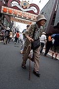 An old woman using a walking cane in Jizo Dori shopping street in Sugamo, Tokyo, Japan. August 14th 2009