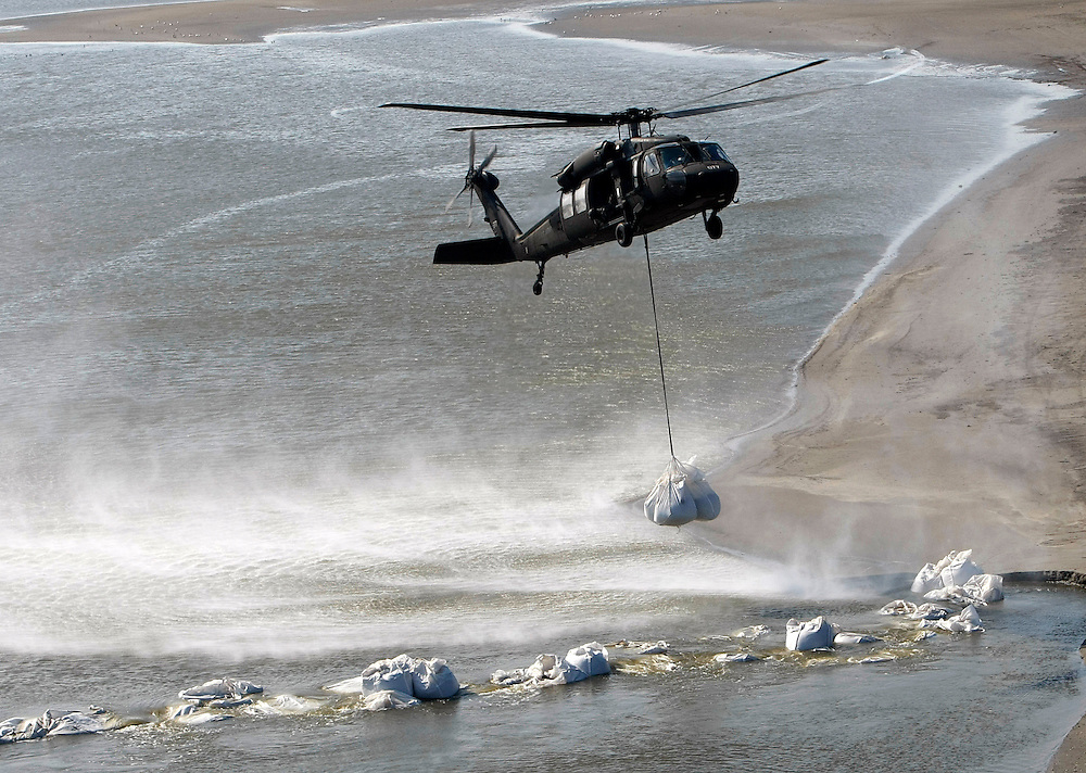 A U.S. Army National Guard helicopter adds a giant sandbag to build a barrier against the BP oil spill offshore from Port Fourchon, Louisiana May 11, 2010. The sandbags were used to fill in breaks in beaches to protect marshes.  REUTERS/Rick Wilking (UNITED STATES)