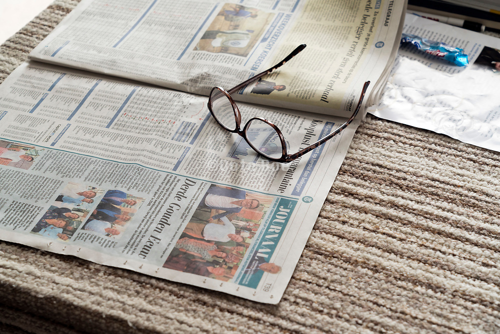 table with reading glasses and newspaper at an elderly person home