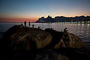 Fishermen on Arporador rock, Ipanema, Rio de Janeiro at dusk, sunset.
