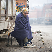 Driver cover with blanket  sitting next to truck during the winter.