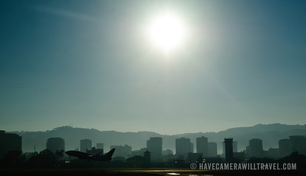 Silhouette of Guatemala City skyline with a plane taking off in bottom left and the mountains in the background against the morning sun taken from Aeropuerto La Aurora (Guatemala City Airport).