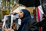 Rally outside Stoke Newington police station, Hackney, where 20 year old Rashan Charles died in custody on 22nd July 2017. Speaker Islington councillor Rakhia Ismail, in front of photo of Rashan Charles and Darren Cumberbatch who died after being arrested in Nuneaton.