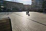 Nederland, Nijmegen, 25-3-2020 Twee mensen, een stel, met een hond, teckel, lopen in het uitgstorven stadscentrum . Om te voorkomen dat groepen mensen dicht bij elkaar komen wordt door politie en boas extra surveillance gehouden . De terrassen zijn afgezet met lint om duidelijk te maken dat daar niet in de zon gezeten mag worden . Foto: Flip Franssen