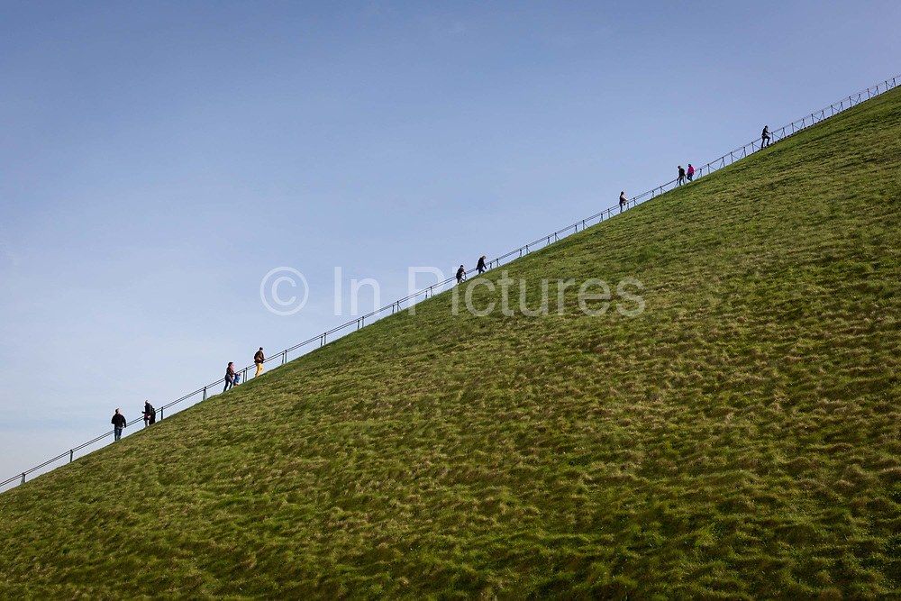 Visitors climb and descend the steep gradient of 225 steps, 43 metre high Waterloo Lions battlefield Mound, on 25th March 2017, at Waterloo, Belgium. The Lions Mound Butte du Lion is a large conical artificial hill completed in 1826. It commemorates the location on the battlefield of Waterloo where a musket ball hit the shoulder of William II of the Netherlands the Prince of Orange and knocked him from his horse during the battle. From the summit, the hill offers a 360 degree vista of the battlefield. The Battle of Waterloo was fought 18 June 1815. A French army under Napoleon Bonaparte was defeated by two of the armies of the Seventh Coalition: an Anglo-led Allied army under the command of the Duke of Wellington, and a Prussian army under the command of Gebhard Leberecht von Blücher, resulting in 41,000 casualties.
