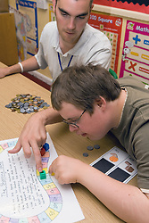 Boy with learning disability and teacher sitting at desk in classroom working on maths problem,