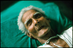 An elderly man lies on his cot, near death, at Mother Teresa's Home for the Dying, in Calcutta, India. The Missions of Charity run this center in Calcutta to care for the elderly and sick. Most of the patients are homeless and sufer from malnutrition and Tuberculosis. Much of the work is done by volunteers who travel to Calcutta from around the world. (Photo © Jock Fistick)