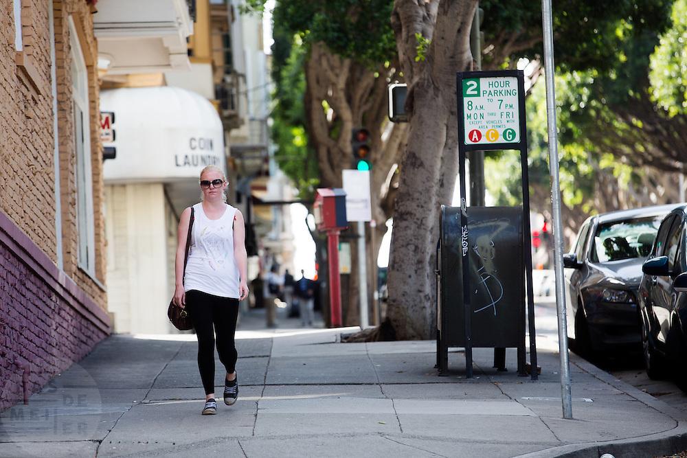 Een meisje loopt door San Francisco. De Amerikaanse stad San Francisco aan de westkust is een van de grootste steden in Amerika en kenmerkt zich door de steile heuvels in de stad.<br /> <br /> A woman is walking in San Francisco. The US city of San Francisco on the west coast is one of the largest cities in America and is characterized by the steep hills in the city.