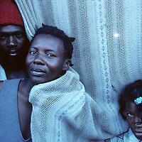 Haiti, Port-au-Prince, Portrait of family standing by curtain covering doorway in Cite Soleil shantytown
