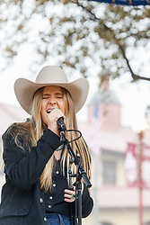 Country music singer in front of Livestock Exchange Building, Fort Worth Stockyards National Historic District, Fort Worth, Texas, USA.