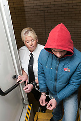 Prisoner being escorted to the transport in cuffs