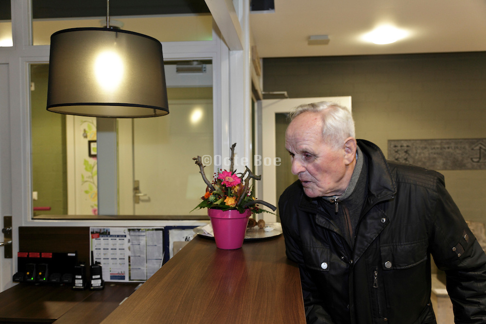 senior man at the front desk inside a retirement home for the elderly