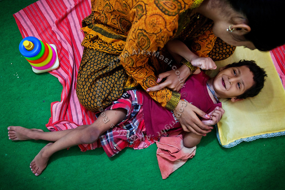 A disabled child is receiving speech therapy inside Chingari Trust, the local NGO caring for disabled  children in Bhopal, Madhya Pradesh, India, near the abandoned Union Carbide (now DOW Chemical) industrial complex.