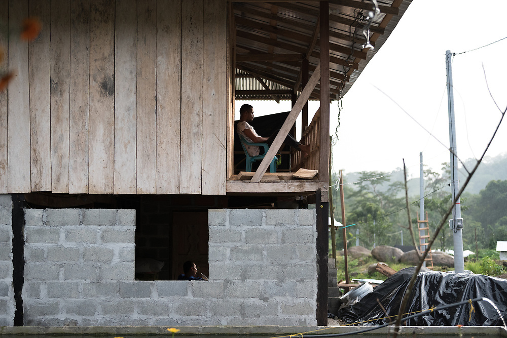 16 November 2018, San José de León, Mutatá, Antioquia, Colombia: As the sun is soon to set, two men sit to rest on different floors of a house in San José de León. Following the 2016 peace treaty between FARC and the Colombian government, a group of ex-combatant families have purchased and now cultivate 36 hectares of land in the territory of San José de León, municipality of Mutatá in Antioquia, Colombia. A group of 27 families first purchased the lot of land in San José de León, moving in from nearby Córdoba to settle alongside the 50-or-so families of farmers already living in the area. Today, 50 ex-combatant families live in the emerging community, which hosts a small restaurant, various committees for community organization and development, and which cultivates the land through agriculture, poultry and fish farming. Though the community has come a long way, many challenges remain on the way towards peace and reconciliation. The two-year-old community, which does not yet have a name of its own, is located in the territory of San José de León in Urabá, northwest Colombia, a strategically important corridor for trade into Central America, with resulting drug trafficking and arms trade still keeping armed groups active in the area. Many ex-combatants face trauma and insecurity, and a lack of fulfilment by the Colombian government in transition of land ownership to FARC members makes the situation delicate. Through the project De la Guerra a la Paz ('From War to Peace'), the Evangelical Lutheran Church of Colombia accompanies three communities in the Antioquia region, offering support both to ex-combatants and to the communities they now live alongside, as they reintegrate into society. Supporting a total of more than 300 families, the project seeks to alleviate the risk of re-victimization, or relapse into violent conflict.