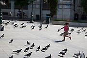 Street scene in Omonia. Girl playing amongst the pigeons in Plateia Kotzia. Athens is the capital and largest city of Greece. It dominates the Attica periphery and is one of the world's oldest cities, as its recorded history spans around 3,400 years. Classical Athens was a powerful city-state. A centre for the arts, learning and philosophy.