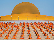 "14 FEBRUARY 2014 - KHLONG LUANG, PATHUM THANI, THAILAND: Buddhist monks sit around the Maha Dhammakaya Cetiya during Makha Bucha Day at Wat Phra Dhammakaya.  The aims of Makha Bucha Day are: not to commit any kind of sins, do only good and purify one's mind. It is a public holiday in Cambodia, Laos, Myanmar and Thailand. Many people go to the temple to perform merit-making activities on Makha Bucha Day. The day marks four important events in Buddhism, which happened nine months after the Enlightenment of the Buddha in northern India; 1,250 disciples came to see the Buddha that evening without being summoned, all of them were Arhantas, Enlightened Ones, and all were ordained by the Buddha himself. The Buddha gave those Arhantas the principles of Buddhism, called ""The ovadhapatimokha"". Those principles are:  1) To cease from all evil, 2) To do what is good, 3) To cleanse one's mind. The Buddha delivered an important sermon on that day which laid down the principles of the Buddhist teachings. In Thailand, this teaching has been dubbed the ""Heart of Buddhism."" Wat Phra Dhammakaya is the center of the Dhammakaya Movement, a Buddhist sect founded in the 1970s and led by Phra Dhammachayo.    PHOTO BY JACK KURTZ"