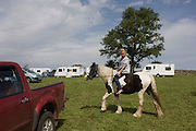A young traveller tries out a new pony at the ancient annual Priddy Sheep (and horse) fair in Somerset, England. The young woman rides bareback around a field on the outskirts of the village. Set in the Mendip Hills, in the south-western English county of Somerset, the Priddy Sheep fair is host to an odd mix of farmers and travellers (commonly and incorrectly known as gypsies). In this field set aside purely for travellers, many with West Country accents but also with nearby Welsh and Irish too, deals are done with a traditional spit on the hand and a smacking of palms, selling a pony to another family. The Priddy Sheep Fair moved from the city of Wells in 1348 because of the Black Death.