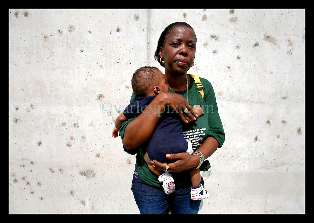 29 August 2006 - New Orleans - Louisiana. Lower 9th ward.  Chevelle Washington (who lost her uncle) and her grandson David (5mts) stands crying beside the newly renovated industrial canal levee flood wall. Civilians gathered at the site of the breach of the industrial canal for the Great Flood commemoration and memorial ceremony to 'honor and remember our loved ones who have passed.' People came to mark the anniversary of devastating hurricane Katrina at the site where the now repaired and allegedly in theory stronger levee flood wall. The levee breached along the industrial canal at the point where people gathered, needlessly killing hundreds of innocent civilians in the worst engineering disaster in US history.